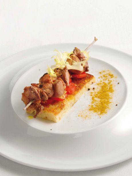 Broqueta de xai marinat sobre 'focaccia' de romaní i escarola