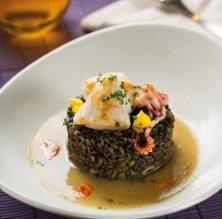 Arròs negre amb crema de calçots i calamarsons, puntets d'allioli de safrà i romesco