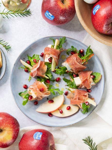Manzanas envueltas en jamón, con queso brie, granada y rúcula